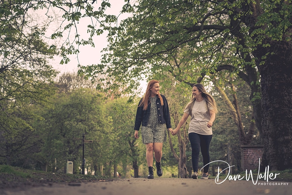 a couple walk through the park on a pre wedding shoot
