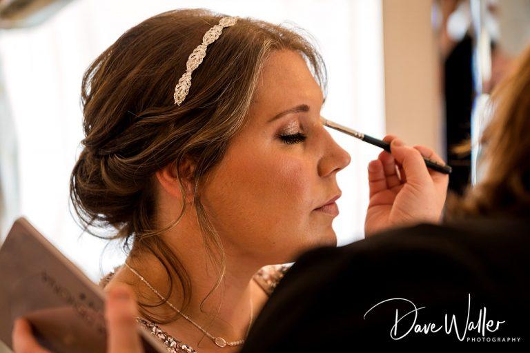 bridesmaid having her make up done before the wedding at Sandhole oak barn